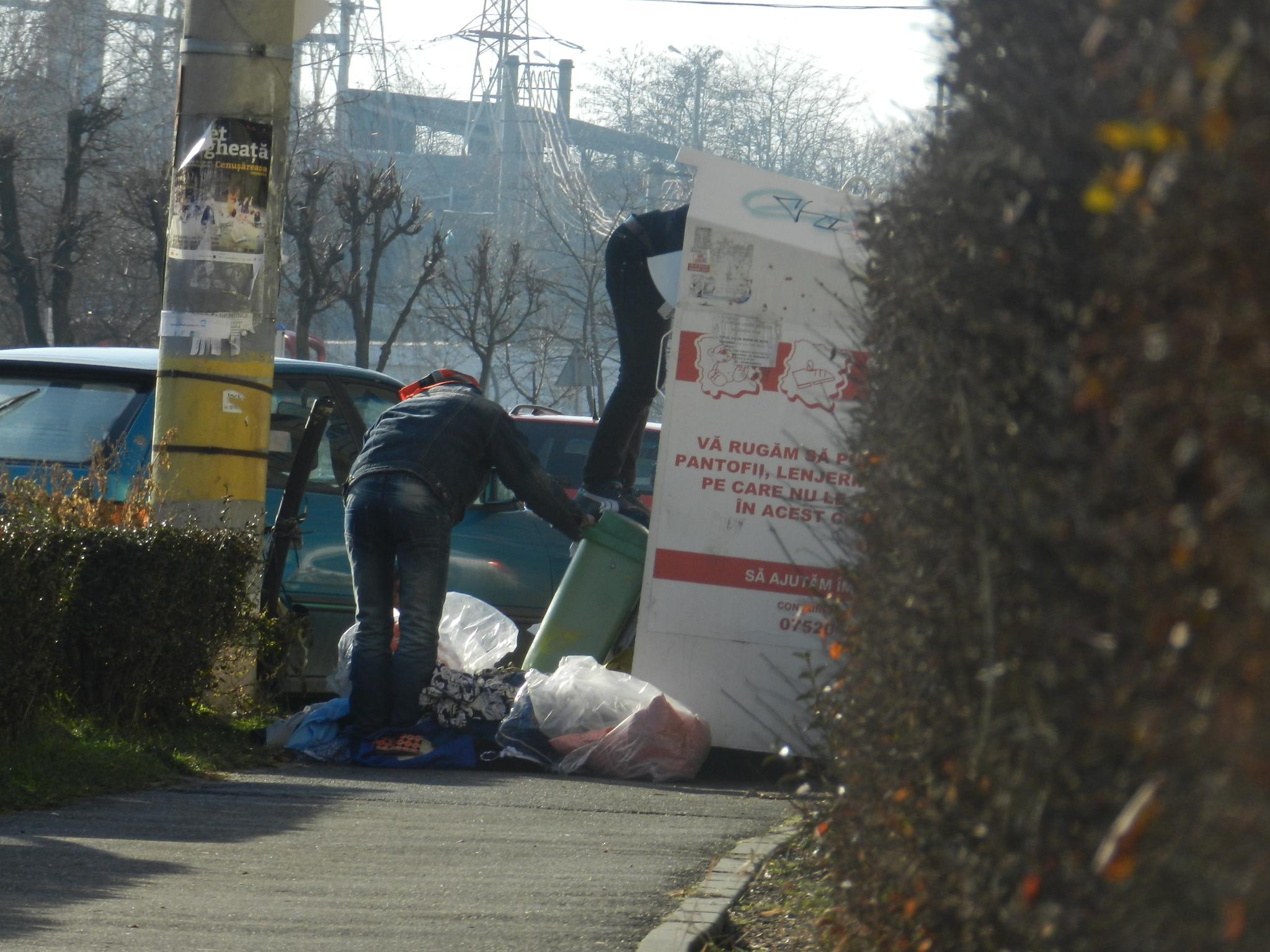 Ziua în amiaza mare, țiganii au dat iama într-un container cu haine pentru oameni săraci. FOTO