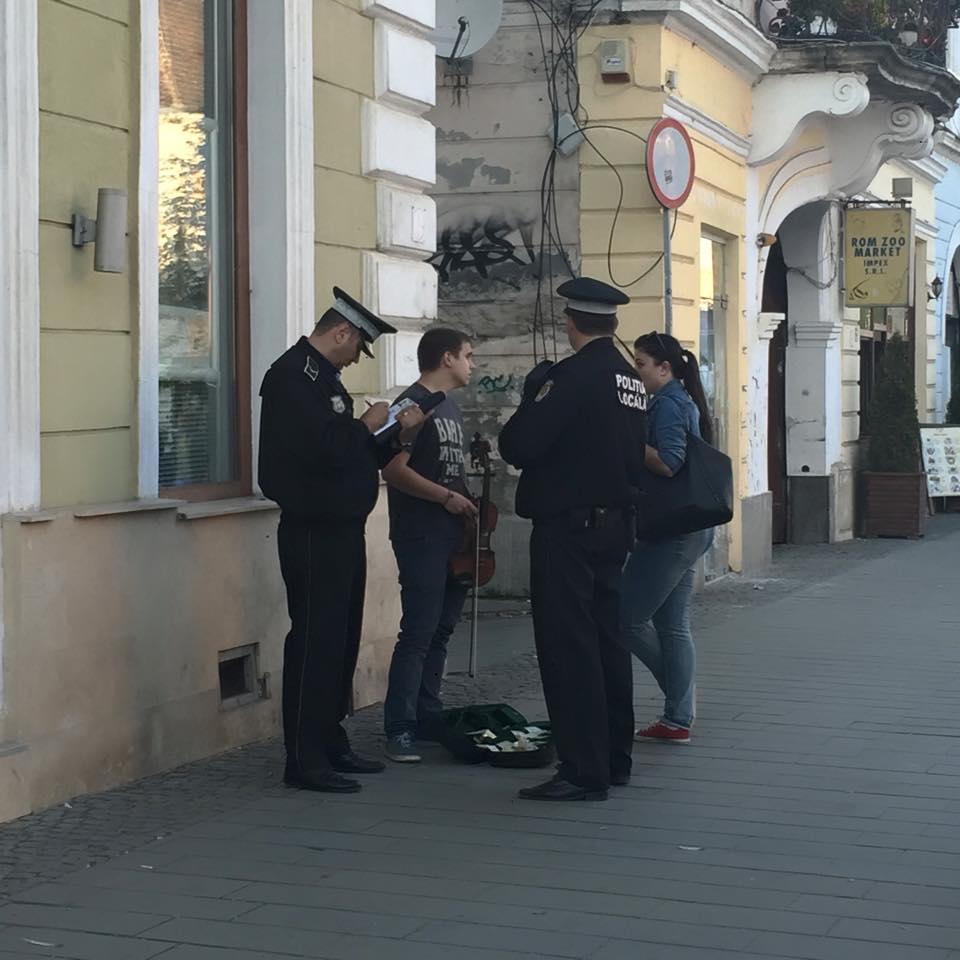Penibilii de serviciu! Doi polițiști de la Locală s-au trezit să amendeze un artist stradal care cânta pe Eroilor! FOTO