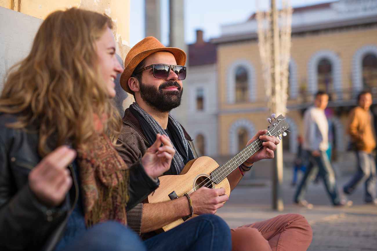 Closeup of young musicians playing ukulele and singing on the street